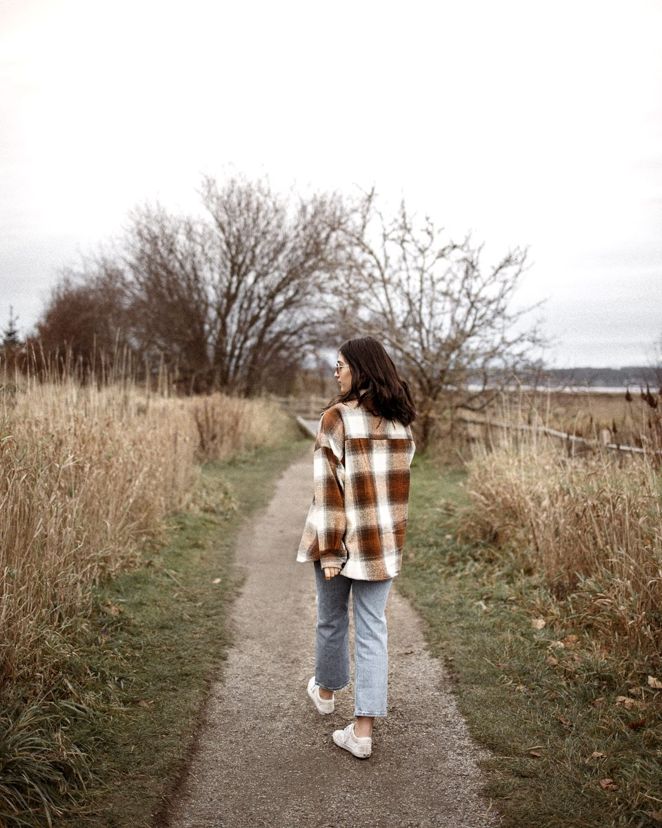 A brunnette girl wearing a shacket, walking on a path with trees.