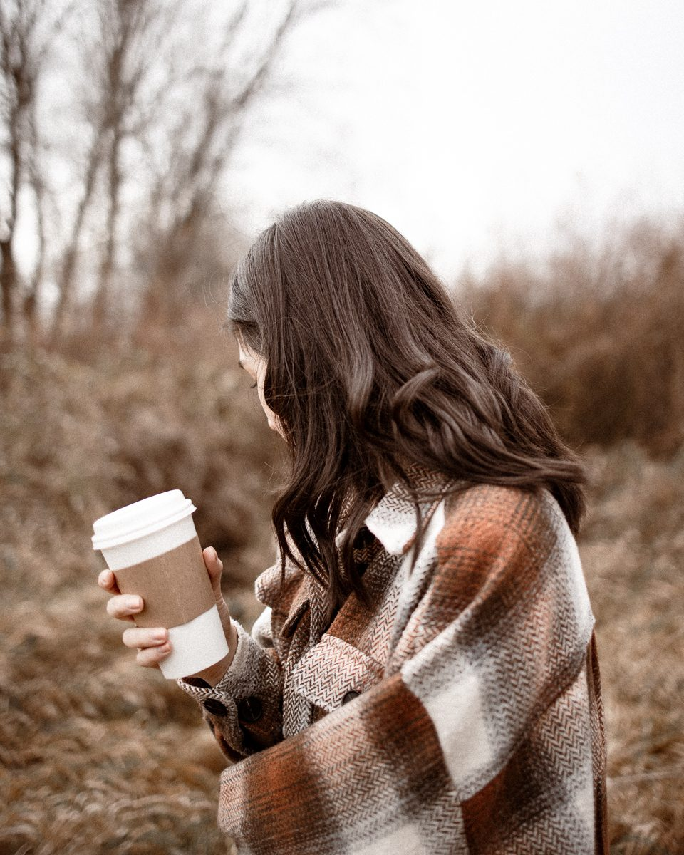 A brunnette girl holding a coffee cup in a field.