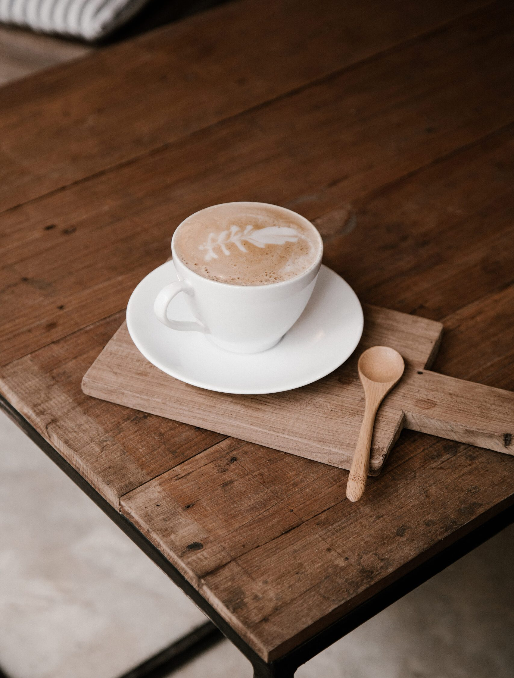 coffee on a brown table with a wooden spoon.