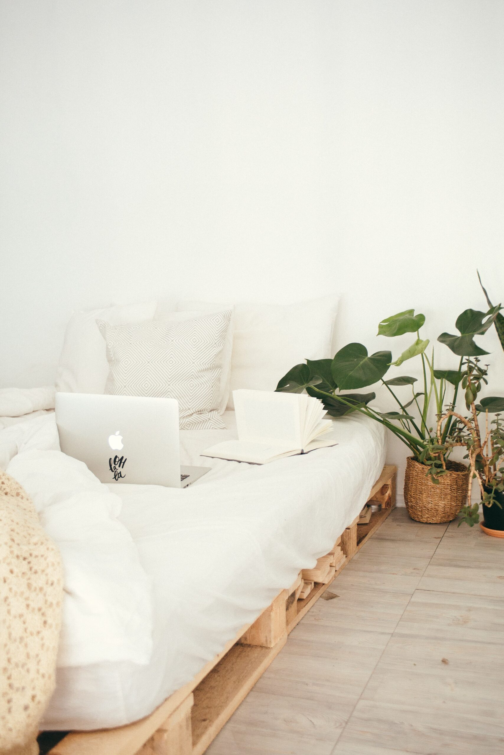 A white bed on wooden pallettes with a macbook laptop and notebook. Green plant beside the bed.